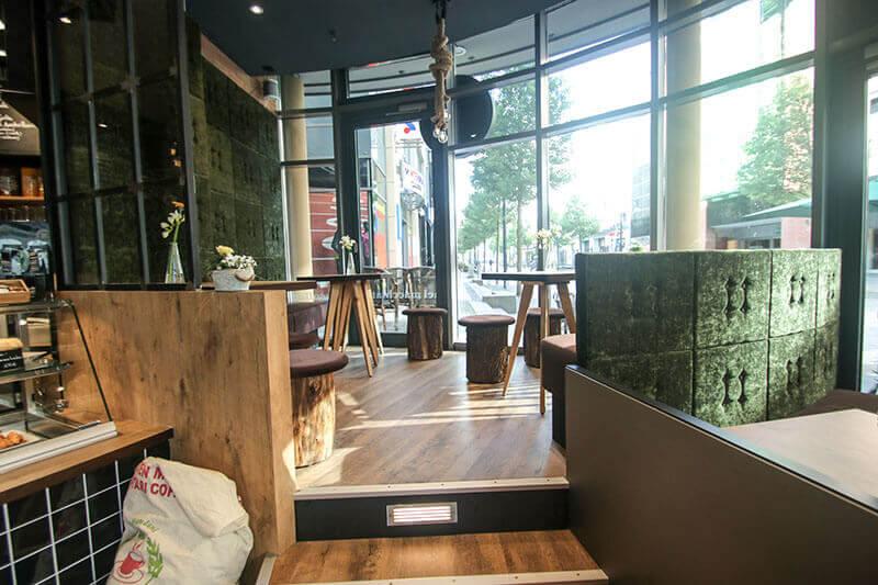 Jan-Mitch Rostock / Baumstamm-Hocker mit Sitzpolster / Sitzbereich auf Podest / Kaffesack-Deko / Bank Raumhoch / Bank als Balustrade / Fliesen schwarz glänzend / Farbmix Eiche und grün