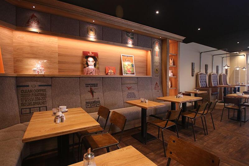 Mahlwerk-Warnemuende / Bank mit Regal / Kaffeesack-Stoffdruck / Schuhputzerstuhl / Sitzbereich Cafe / Stahlrohrstuhl / Metall / Vintage / rustikal / modern / Eichentischplatte