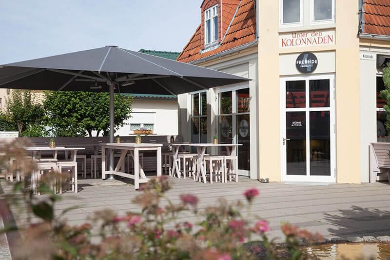4-Freunde-und-Craft_Kuehlungsborn-132_Terrasse_Stehtischbereich_Grossschirm_Terrassenschirm-Gastronomie_Holzbank-Outdoor-Terrasse-mit-Polster