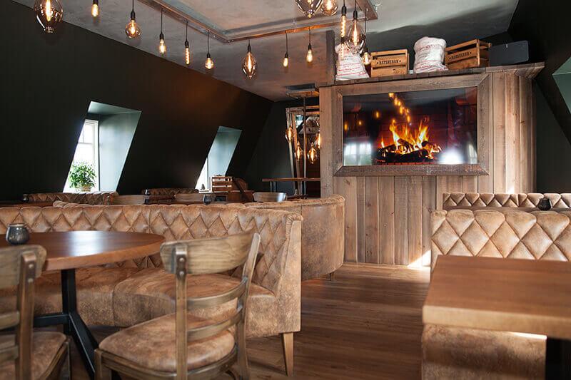 4-Freunde-und-Craft_Kuehlungsborn-74_Gastraum-Dachgeschoss-mit-Schraege_rusitkal-modern_Rundbank-Gastronomie_Wandverkleidung-mit-Bildschirm